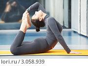 Красивая молодая женщина в сером спортивном костюме занимается гимнастикой в тренажёрном зале. Стоковое фото, фотограф Дмитрий Калиновский / Фотобанк Лори