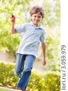 Радостный мальчик бежит с игрушечным самолетиком. Стоковое фото, фотограф Monkey Business Images / Фотобанк Лори