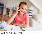 Купить «Улыбающаяся девочка разговаривает по мобильному телефону за письменным столом», фото № 3060391, снято 29 января 2006 г. (c) Monkey Business Images / Фотобанк Лори