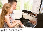 Купить «Мальчик с девочкой играют на пианино», фото № 3060519, снято 3 мая 2007 г. (c) Monkey Business Images / Фотобанк Лори