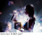 Купить «Силуэт женщины, открывающей подарок на фоне огней», фото № 3061227, снято 12 декабря 2011 г. (c) Константин Юганов / Фотобанк Лори