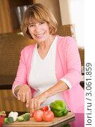 Купить «Улыбающаяся женщина готовит овощной салат», фото № 3061859, снято 27 июня 2007 г. (c) Monkey Business Images / Фотобанк Лори