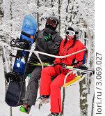 Мужчина и женщина в горнолыжных костюмах на подъёмнике на фоне заснеженного леса (2010 год). Редакционное фото, фотограф Александр Фемяк / Фотобанк Лори