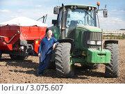 Купить «Тракторист и зеленый трактор с красным прицепом», фото № 3075607, снято 19 мая 2000 г. (c) Monkey Business Images / Фотобанк Лори