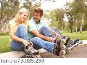 Купить «Улыбающаяся молодая пара на роликах отдыхает в парке», фото № 3085259, снято 13 августа 2009 г. (c) Monkey Business Images / Фотобанк Лори