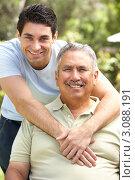 Купить «Улыбающийся молодой мужчина обнимает отца на свежем воздухе», фото № 3088191, снято 9 августа 2009 г. (c) Monkey Business Images / Фотобанк Лори