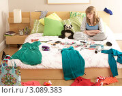 Купить «Девочка-подросток сидит на кровати в комнате с беспорядком», фото № 3089383, снято 30 апреля 2009 г. (c) Monkey Business Images / Фотобанк Лори