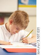 Купить «Мальчик за партой пишет в тетрадке», фото № 3107031, снято 16 февраля 2010 г. (c) Monkey Business Images / Фотобанк Лори