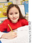Купить «Девочка улыбается в классе за партой с ручкой в руке», фото № 3107147, снято 16 февраля 2010 г. (c) Monkey Business Images / Фотобанк Лори