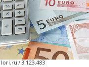 Купить «Купюры евро и лежащий сверху калькулятор, крупно», фото № 3123483, снято 16 августа 2011 г. (c) Monkey Business Images / Фотобанк Лори