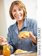 Купить «Женщина среднего возраста ест круассаны», фото № 3124667, снято 7 мая 2011 г. (c) Monkey Business Images / Фотобанк Лори