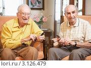 Двое пожилых мужчин с мобильными телефонами сидят в креслах в гостиной и улыбаются. Стоковое фото, фотограф Monkey Business Images / Фотобанк Лори