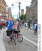 Купить «Велотуристы в Амстердаме фотографируют городские достопримечательности», фото № 3150807, снято 12 сентября 2010 г. (c) FMRU / Фотобанк Лори