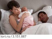 Купить «Семейная пара в кровати - женщина держит на руках грудного ребенка», фото № 3151887, снято 8 января 2011 г. (c) Monkey Business Images / Фотобанк Лори