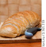 Нарезанный батон белого хлеба и нож на разделочной доске. Стоковое фото, фотограф Игорь Низов / Фотобанк Лори