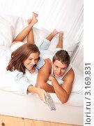 Купить «Мужчина и женщина лежат на кровати перед телевизором», фото № 3169831, снято 12 августа 2009 г. (c) CandyBox Images / Фотобанк Лори