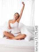 Купить «Очаровательная шатенка с mp3-плеером сидит на кровати среди белых подушек», фото № 3175643, снято 7 августа 2009 г. (c) CandyBox Images / Фотобанк Лори