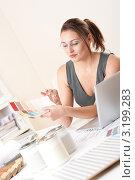 Купить «Озадаченная дизайнер интерьера сидит за столом и смотрит на палитру цветов», фото № 3199283, снято 16 ноября 2009 г. (c) CandyBox Images / Фотобанк Лори