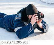 Мужчина фотограф  с фотоаппаратом лежит на снегу (2012 год). Редакционное фото, фотограф Игорь Низов / Фотобанк Лори