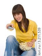 Купить «Девушка переключает каналы и держит миску с попкорном», фото № 3211539, снято 11 марта 2010 г. (c) CandyBox Images / Фотобанк Лори