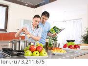 Купить «Парень и девушка  с кулинарной книгой готовят еду вдвоем», фото № 3211675, снято 30 марта 2010 г. (c) CandyBox Images / Фотобанк Лори