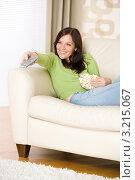 Купить «Радостная шатенка переключает каналы пультом, сидя на диване с попкорномм», фото № 3215067, снято 16 мая 2010 г. (c) CandyBox Images / Фотобанк Лори