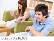Купить «Эмоциональный парень увлеченно переключает ТВ-каналы», фото № 3216079, снято 17 апреля 2010 г. (c) CandyBox Images / Фотобанк Лори