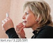 Женщина перед ручным зеркалом красит губы контурным карандашом. Стоковое фото, фотограф Игорь Низов / Фотобанк Лори