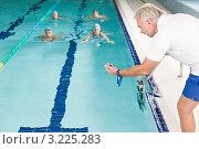 Купить «Молодые люди в бассейне плавают на скорость, рядом с бассейном тренер с секундомером», фото № 3225283, снято 18 сентября 2010 г. (c) CandyBox Images / Фотобанк Лори
