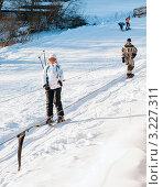Купить «Девушка на лыжах поднимается в гору, держась за подъёмник», эксклюзивное фото № 3227311, снято 5 февраля 2012 г. (c) Игорь Низов / Фотобанк Лори