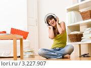 Веселая девушка сидит на полу в комнате и слушает музыку в наушниках. Стоковое фото, фотограф CandyBox Images / Фотобанк Лори