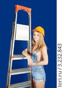 Девушка в строительной каске и джинсовом комбинезоне стоит около стремянки на синем фоне. Стоковое фото, фотограф Яков Филимонов / Фотобанк Лори