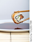 Ролл держут палочками над тарелкой с соевым соусом. Стоковое фото, фотограф Наталия Китаева / Фотобанк Лори