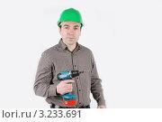 Мужчина в зеленой каске и с дрелью в руках. Стоковое фото, фотограф Владимир Одегов / Фотобанк Лори