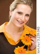 Купить «Красивая девушка в коричневой кофте держит три подсолнуха в руках», фото № 3239043, снято 23 февраля 2011 г. (c) CandyBox Images / Фотобанк Лори