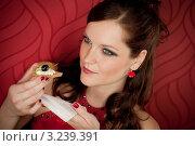 Купить «Молодая женщина в красном вечернем платье ест легкую закуску», фото № 3239391, снято 26 февраля 2011 г. (c) CandyBox Images / Фотобанк Лори