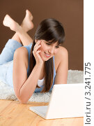 Темноволосая девушка с челкой лежит на полу с ноутбуком. Стоковое фото, фотограф CandyBox Images / Фотобанк Лори