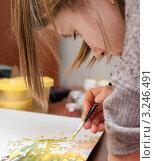 Купить «Девочка склонившись над рисунком  рисует за столом  красками», эксклюзивное фото № 3246491, снято 3 февраля 2012 г. (c) Игорь Низов / Фотобанк Лори