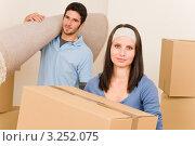 Переезд. Девушка и парень несут ковер и картонную коробку. Стоковое фото, фотограф CandyBox Images / Фотобанк Лори