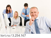 Купить «Довольный деловой человек в офисе, на заднем плане трое коллег по работе», фото № 3254167, снято 27 августа 2011 г. (c) CandyBox Images / Фотобанк Лори