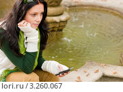 Купить «Девушка у фонтана задумчиво держит мобильный телефон в руках (крупный план)», фото № 3260067, снято 28 сентября 2011 г. (c) CandyBox Images / Фотобанк Лори