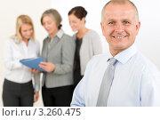 Купить «Уверенный менеджер средних лет на фоне обсуждающих документы женщин», фото № 3260475, снято 8 октября 2011 г. (c) CandyBox Images / Фотобанк Лори