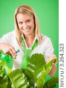 Купить «Улыбающаяся молодая блондинка опрыскивает растения», фото № 3264323, снято 24 ноября 2011 г. (c) CandyBox Images / Фотобанк Лори