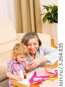 Купить «Улыбающаяся бабушка помогает своей внучке делать аппликацию», фото № 3264835, снято 10 января 2012 г. (c) CandyBox Images / Фотобанк Лори