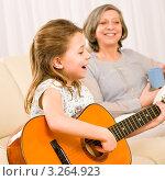 Купить «Маленькая девочка играет на гитаре и поет на фоне счастливой бабушки», фото № 3264923, снято 10 января 2012 г. (c) CandyBox Images / Фотобанк Лори