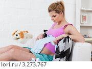 Молодая беременная женщина с детской одеждой сидит на диване дома, фото № 3273767, снято 17 января 2012 г. (c) Мельников Дмитрий / Фотобанк Лори