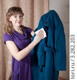 Купить «Счастливая девушка чистит пальто», фото № 3282203, снято 18 февраля 2012 г. (c) Яков Филимонов / Фотобанк Лори