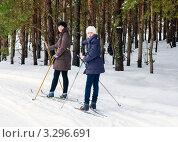 Счастливая семья. Дочка и мама на лыжах стоят на фоне сосен и смотрят назад. Стоковое фото, фотограф Игорь Низов / Фотобанк Лори