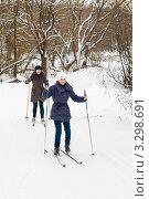 Счастливая семья.Дочка и мама на лыжах едут по дороге по зимнему лесу (2012 год). Редакционное фото, фотограф Игорь Низов / Фотобанк Лори