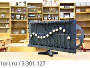 Купить «Модель колебания волн на парте в пустом классе физики на фоне стеллажей с книгами», фото № 3301127, снято 14 октября 2010 г. (c) Losevsky Pavel / Фотобанк Лори